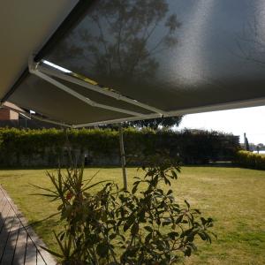 toldo de brazo articulado con tejido screen en un jardín